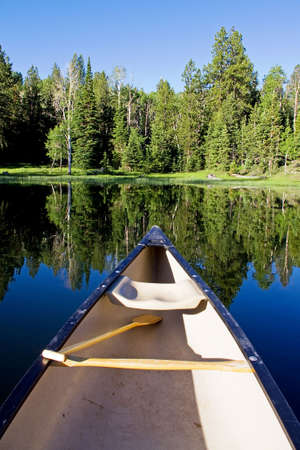 A wooden paddle rests in a canoe on a blue mountain lake.