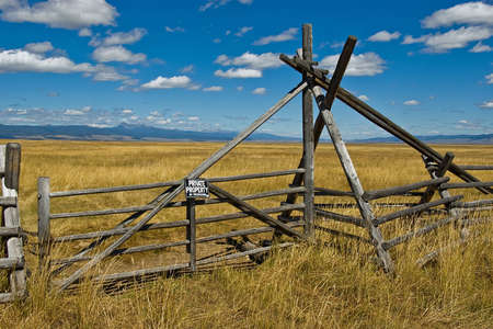 A rustic ranch gate with a private property sign. photo