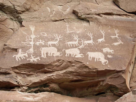 Ancient carvings of an animal herd with hunters. Stock Photo