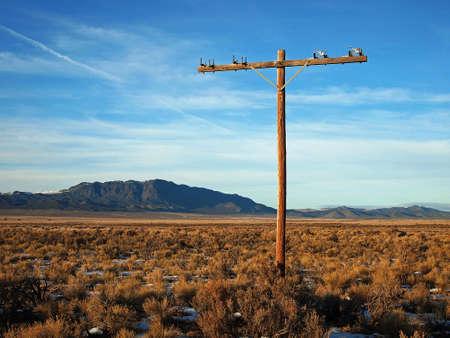 Een verlaten macht pole in een lege, hoge woestijn landschap. Stockfoto