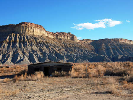 butte: An abandoned shack in front of a rugged butte. Stock Photo
