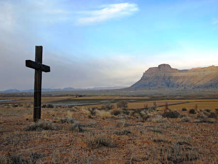 A wooden cross stands on a hillside overlooking a desert butte.