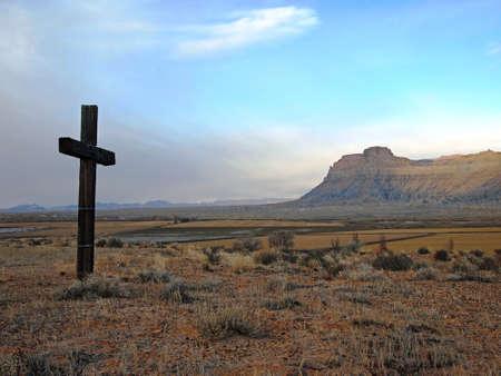 A wooden cross stands on a hillside overlooking a desert butte.