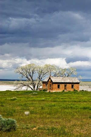 An abandoned farm house stands above a dry lake. photo