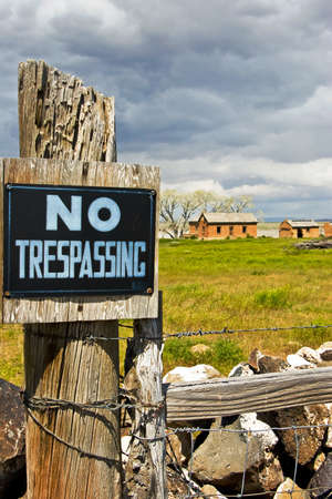 A NO TRESPASSING sign on a fence blocks access to an abandoned farm. Stock Photo