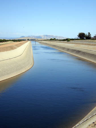 Irrigation water flows in a canal near an orange grove