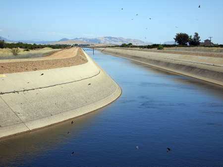 Irrigation water being pumped from reservoirs, through a canal, to agricultural fields.