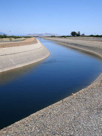 reservoirs: Irrigation water being pumped from reservoirs, through a canal, to agricultural fields.