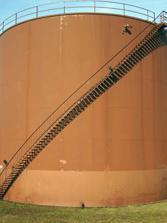 An external staircase curves to the top of an industrial fuel tank.