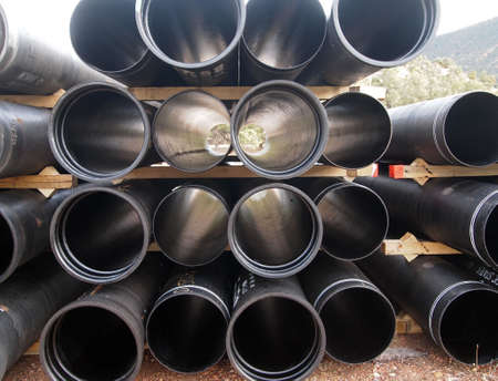 A stack of steel pipes at a construction site. Imagens