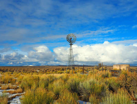An old wind mill pumps water in ranch country. Imagens - 51352660