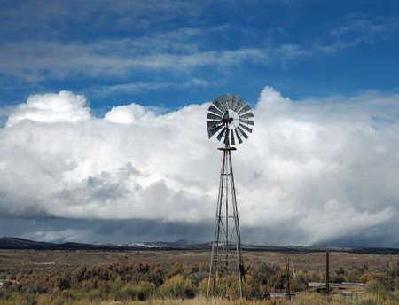 An old wind mill pumps water in ranch country.