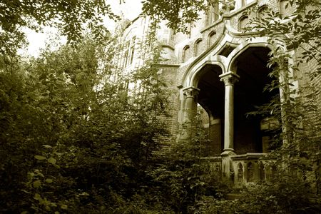 19th century: The overgrown entrance of an old, forgotten castle ruin in Europe,