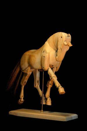 drafje: Een houten paard model in draf, over een zwarte achtergrond. Stockfoto