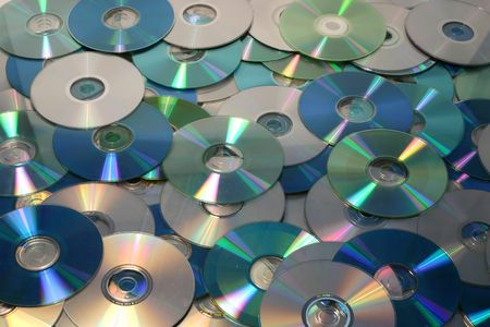 dvdrw: A background image filled with several cds, cdroms and dvds