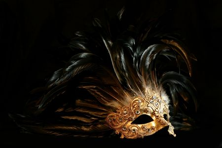 A luxurious golden mask with long feathers on a black background Stock Photo