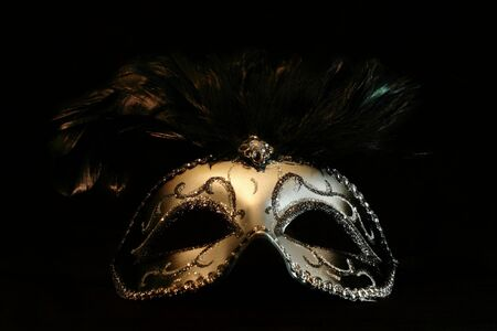 costume ball: A black and silver mask isolated on a black background