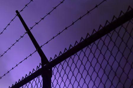 A dark iron fence, dark smoke in the background photo