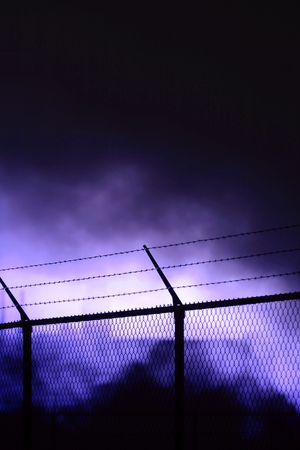 A black fence, threathening smoke in the background Stock Photo