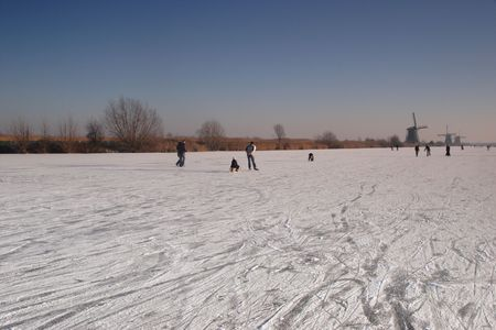 Skaters on the ice at Kinderdijk, The Netherlands. Several windmills visible against a clear blue sky. Stock Photo - 2423101