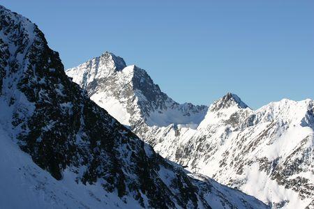 wintersport: Snowy peaks against a clear blue sky in winter. Stock Photo