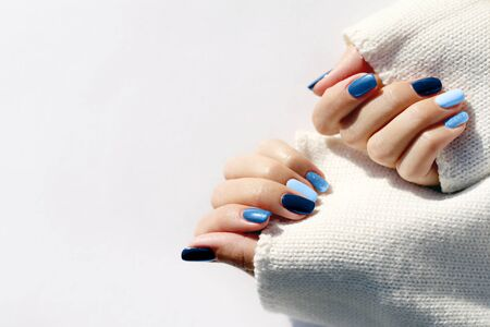 Manicured womans hands in warm white sweater. Inspired by classic blue -color of the year 2020.
