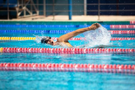 Triathlon fitness athlete training swimming front crawl style in the swimming pool with clear blue water. Stockfoto