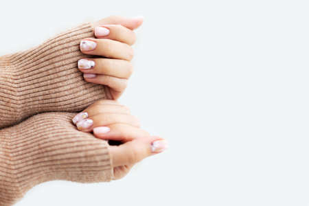 Warm atmosphere. Manicured womans hands in warm white sweater.