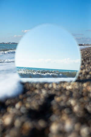 Hope, freedom and escape concept. Sea in the reflection of the round mirror standing on the beach. Travel concept. Copy space. 免版税图像