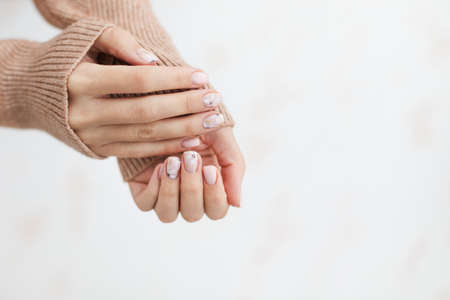 Female hand manicure close up view with warm sweater on light background.
