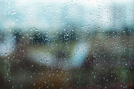 Rain drops on window glass surface. Rainy spring background