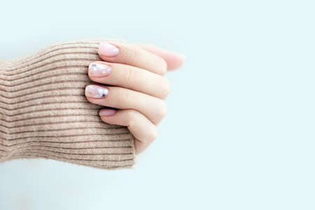 Pastel beige manicure on the light background. Manicured nails and soft hands skin with copy space. Womans hands in warm sweater. Standard-Bild