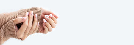 Pastel beige manicure on the light background. Manicured nails and soft hands skin salon banner with copy space. Womans hands in warm sweater.