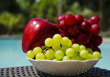 Red apple and grape in white plate on table by the swimming pool