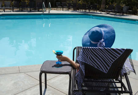 Girl in blue hat with coctail drink by the pool