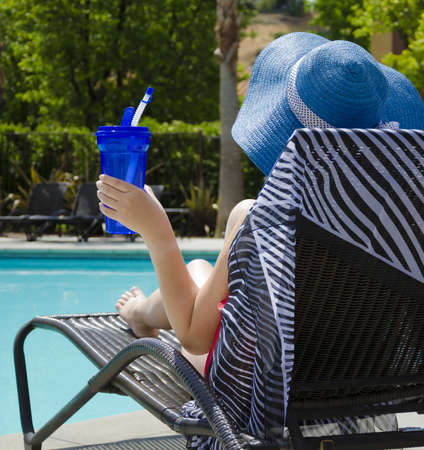 Girl in blue hat with coctail drink by the pool photo