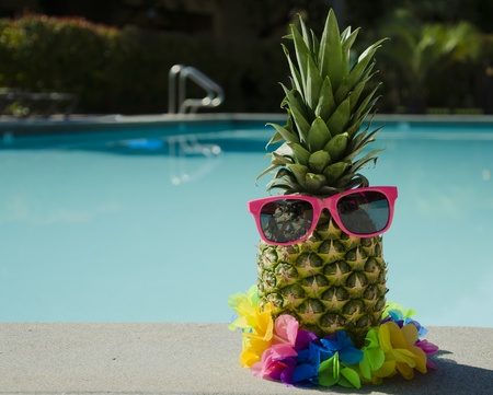 Funny pineapple in sunglasses by the pool Stock Photo