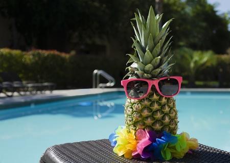 Funny pineapple in sunglasses by the pool Zdjęcie Seryjne
