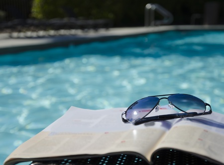 Sunglasses on a magazine by the swimming pool