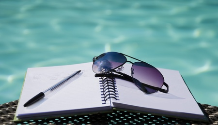 Sunglasses and pen on a note-pad  by the swimming pool