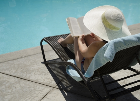 Girl in a summer heat reading a book by the swimming pool
