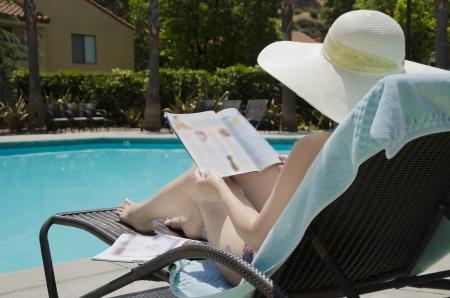 magazin: Chica en un calor de verano est� leyendo un magazin de la piscina