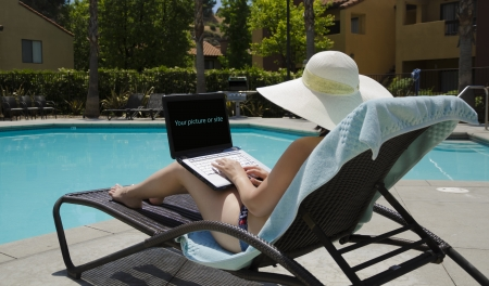Girl in a summer heat typing on laptop by the swimming pool