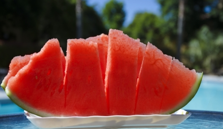 Few peaces of watermelon in white plate on table by the swimming pool