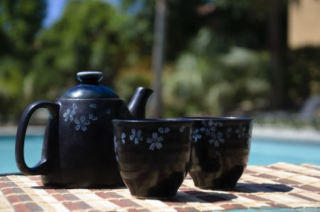 tetsubin: Asian Teapot and two tea cups on table by the swimming pool