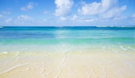 Gentle wave on the sandy Poipu beach in Hawaii, Kauai