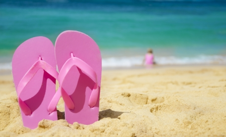 Flip flops on sandy beach with playing girl by the sea on background (Hawaii, Kauai)