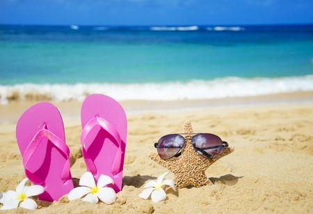 Flip flops and starfish with sunglasses with tropical flowers on sandy beach in Hawaii, Kauai Stock Photo