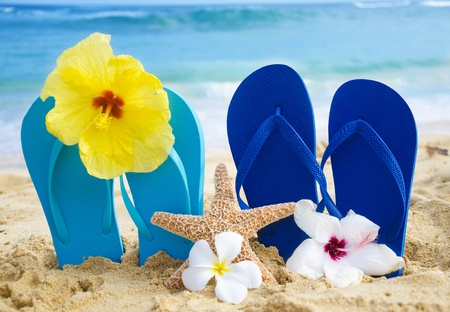 Flip flops and starfish with tropical flowers on sandy beach in Hawaii