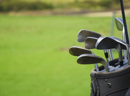 Golf bag with clubs after play on green grass background
